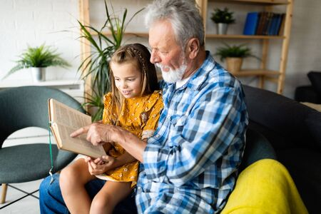 Bearded grandfather and his grandchild are having fun reading a book together 写真素材