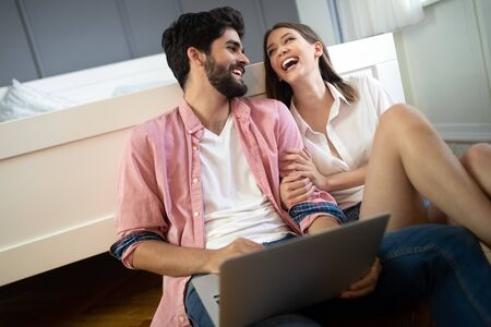 Young couple relaxing on bed with laptop. Love, technology, happiness, people and fun concept. 스톡 콘텐츠
