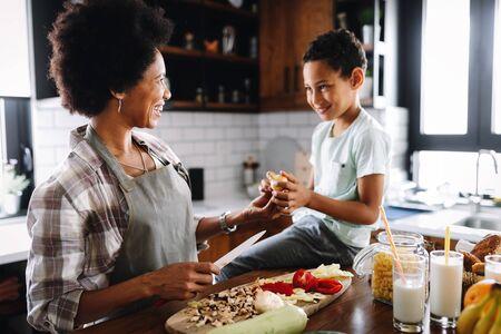 Madre e hijo se divierten preparando comida sana en la cocina Foto de archivo