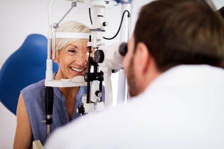 Optometrist examining senior woman in modern ophthalmology clinic