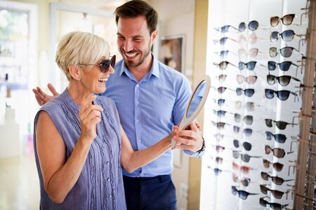 Health care, people, eyesight and vision concept. Mature woman choosing glasses at optics store