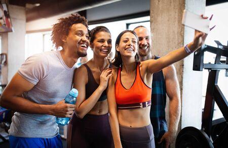 Grupo de amigos divirtiéndose en el gimnasio, haciendo un selfie