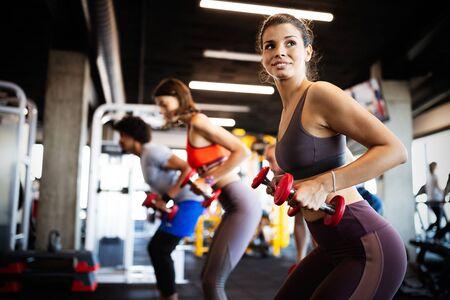 Gezonde jonge mensen die oefeningen doen bij fitnessstudio.