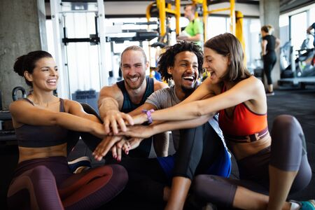 Happy fit friends exercising, working out in gym to stay healthy together Archivio Fotografico