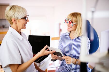 Senior woman optometrist examining patient in modern ophthalmology clinic 스톡 콘텐츠
