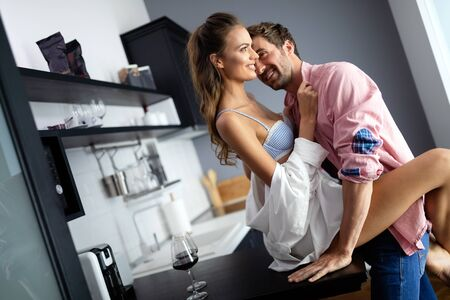 Beautiful passionate couple is having sex in kitchen