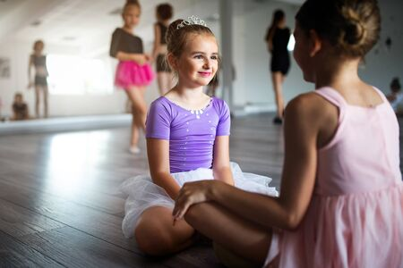 Group of fit happy children exercising ballet in studio together Stock Photo
