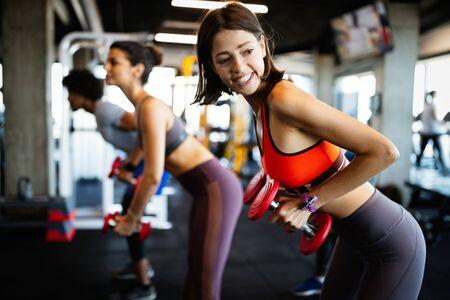 Bellissime persone in forma che si allenano insieme in palestra