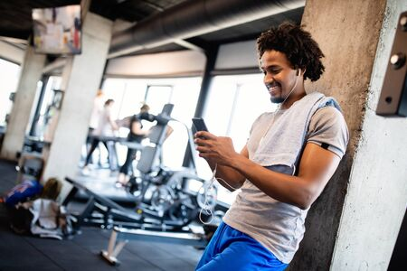 Young muscular man using mobile phone at the gym in exercise break 版權商用圖片