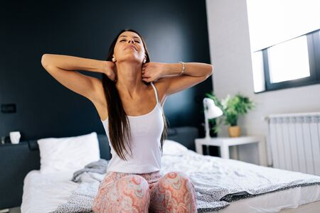 Young woman sitting on the bed with pain in neck Stockfoto - 135490353