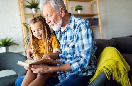 Bearded grandfather and his grandchild are having fun reading a book together Stock Photo