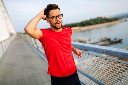 Handsome young man running across the bridge. Stock Photo