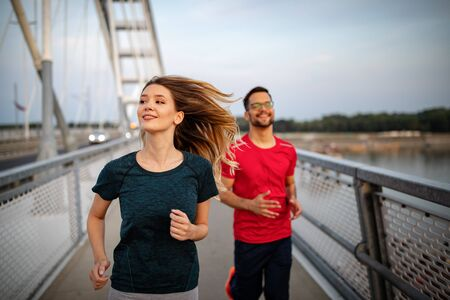 Early morning workout. Happy couple running across the bridge