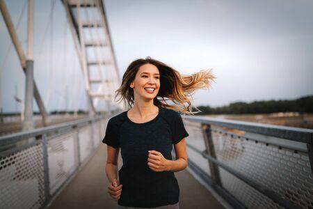 Beautiful fit happy runner woman crossing bridge