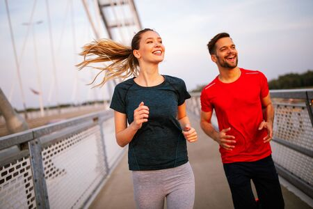 Fitness, sport, people, exercising and lifestyle concept. Couple running outdoor