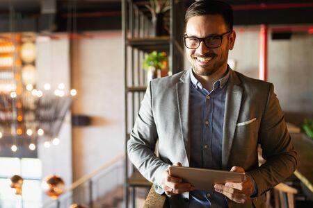 Heureux homme d'affaires vêtu d'un costume dans un bureau moderne à l'aide d'une tablette