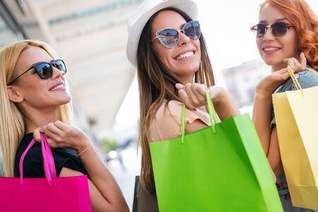 Felicità, amici, shopping e divertimento concetto-sorridente giovani donne con borse della spesa.