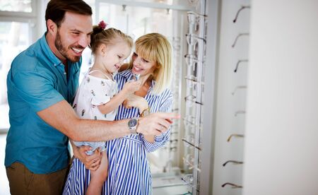 Happy family choosing glasses in optics store