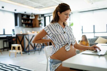 Donna incinta stanca che lavora da casa al computer