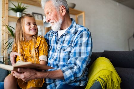 Grandfather reading book with his granddaughter at home. Happy family time Stock Photo