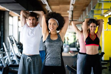 Group of fit young people at the gym exercising