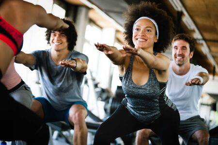 Beautiful fit people friends exercising together in gym Stock Photo