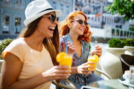 Vrienden hebben een geweldige tijd in café. Vrouwen glimlachen en drinken sap en genieten samen