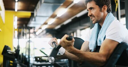 Healthy life and gym exercise concept. Fit man working out in sport fitness club