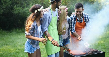 Group of friends making barbecue in Standard-Bild - 140186193