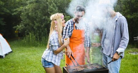 Friends making barbecue and having lunch Standard-Bild - 140189780