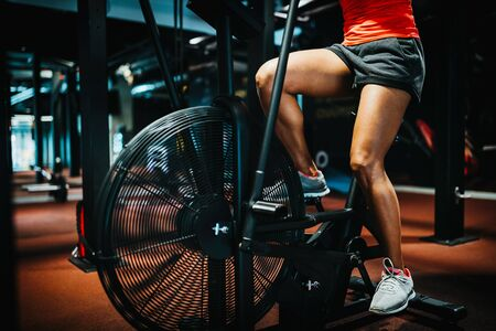 Fitness female using air bike for cardio workout at crossfit gym.