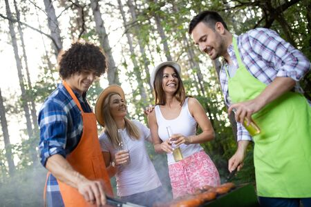 Friends having a barbecue party in nature while having fun Banco de Imagens
