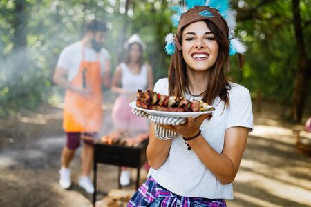 Friends having a barbecue party and fun in nature