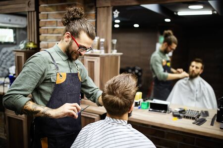 Young bearded man getting haircut by hairdresser while sitting in chair at barbershop Banco de Imagens