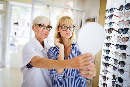 Gesundheitswesen, Menschen, Sehkraft und Vision-Konzept. Frau mit Optiker, die eine Brille auswählt