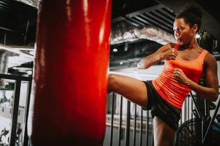 Beautiful fit woman in sportswear boxing kicking bag in the gym. Stock Photo
