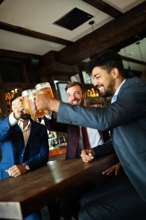 Group of happy friends drinking beer at the pub and having fun Standard-Bild