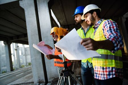 Architect and construction engineer or surveyor discussion plans and blueprints
