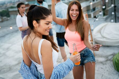 Having a great time with friends, having fun at rooftop party Imagens