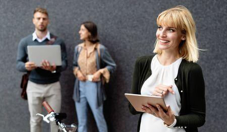 Groupe de jeunes gens d'affaires détenant différents appareils numériques en plein air Banque d'images