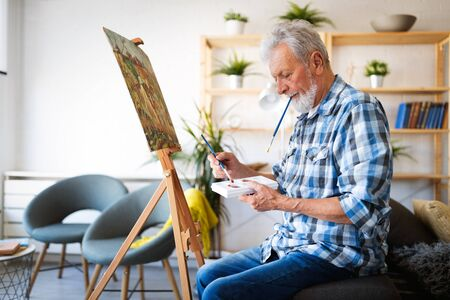Happy retired man painting on canvas for fun at home