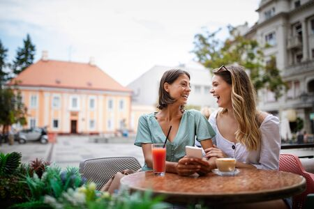 Technology, friendship and people concept. Happy young women with smartphone at outdoor cafe Foto de archivo