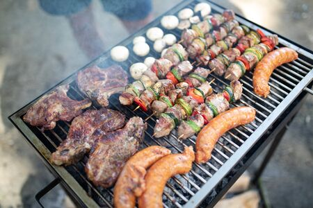 Selection of meat grilling over the coals on a portable barbecue Foto de archivo
