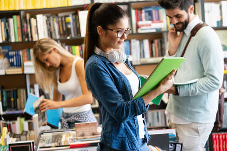 Education concept. University students preparing for exam, talking in library