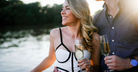 Summer holidays and dating concept. Happy romantic couple in love hugging with champagne