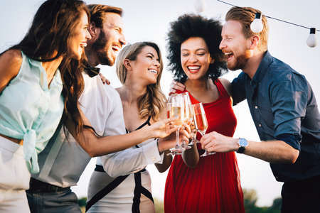 Group of happy friends partying and toasting drinks