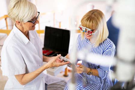 Senior woman optometrist examining patient in modern ophthalmology clinic Stockfoto