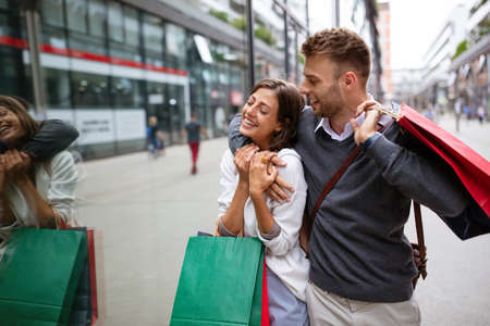 Cheerful successful happy young lovely couple with shopping bags traveling and laughing Stock Photo