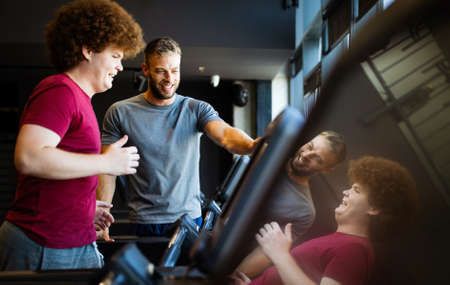 Fat young men with trainer exercising at fitness gym.