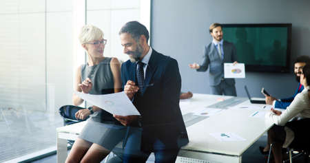 Portrait of happy business people discussing together in office
